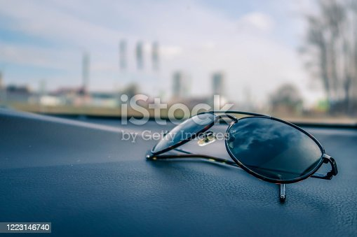 Black eyeglasses on black textured car dashboard in selective focus against blur background through windshield