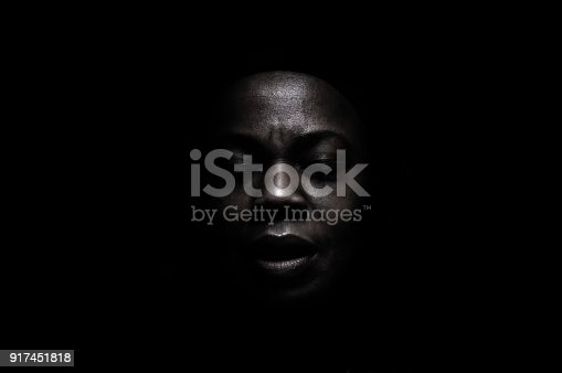 Black face in deep shadow , powerful expression.