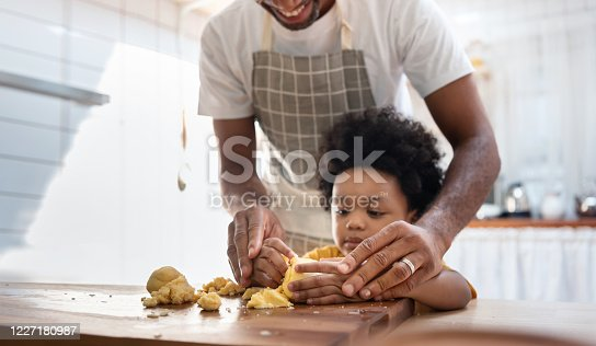 Black family having fun prepare bakery together at home. African American father and adorable son kneading dough in kitchen. Happy loving Man and little helper boy enjoy while making cakes and cookies