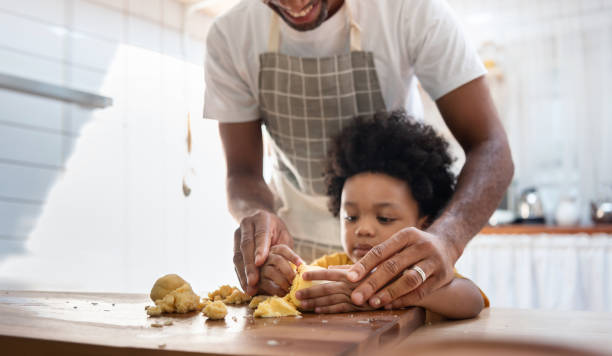 Black family having fun prepare bakery together at home. African American father and adorable son kneading dough in kitchen. Happy loving Man and little helper boy enjoy while making cakes and cookies stock photo