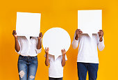 Different opinions. Afro family of three holding empty speech bubbles in front of their heads, standing over yellow background.