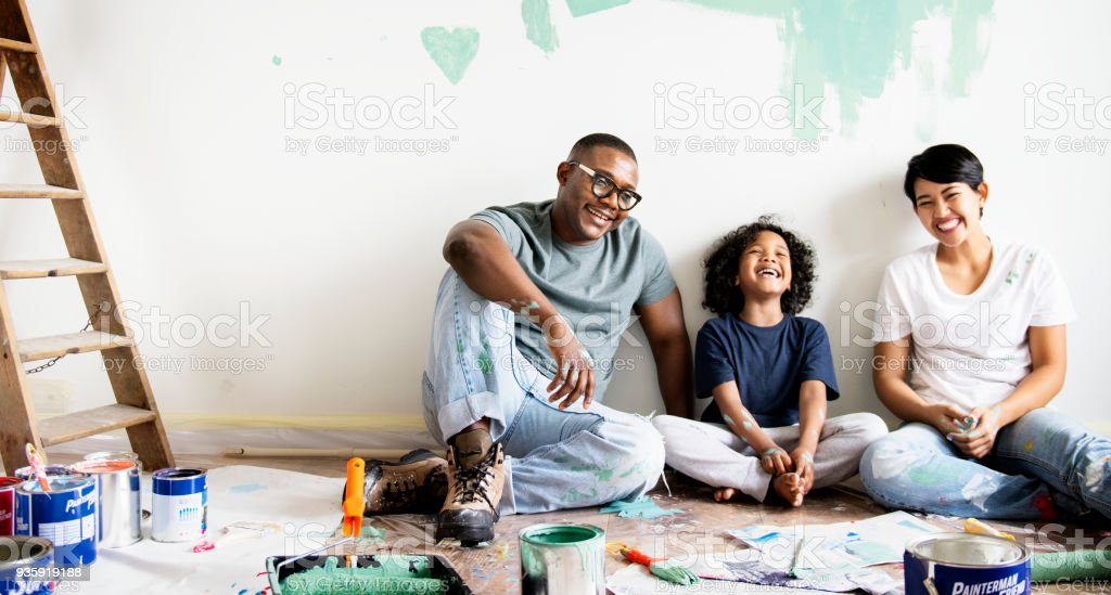 Black family painting house wall stock photo