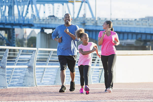 Black family staying fit, power walking on waterfront - Photo