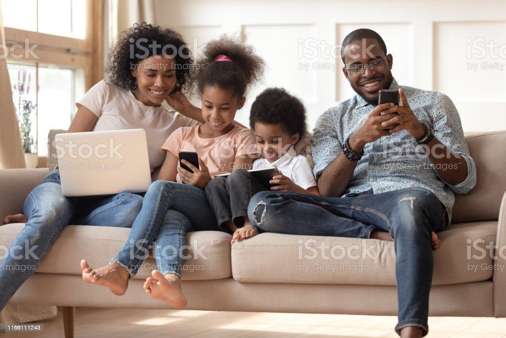 Black family with kids relax on couch using gadgets - Zbiór zdjęć royalty-free (Afrykanin)