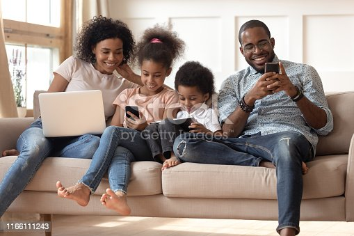 Happy young african American family with preschooler kids sit on couch use gadgets together, smiling black modern parents spend time with small children play on electronic devices. Technology concept