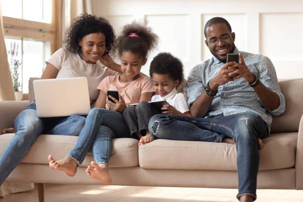 czarna rodzina z dziećmi relaksuje się na kanapie za pomocą gadżetów - przemysł elektroniczny zdjęcia i obrazy z banku zdjęć