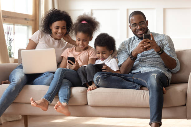 black family with kids relax on couch using gadgets - electronics industry stock pictures, royalty-free photos & images