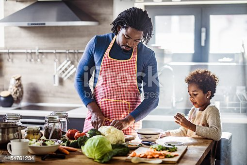 African American single father cooperating with his small daughter while preparing a meal in the kitchen.