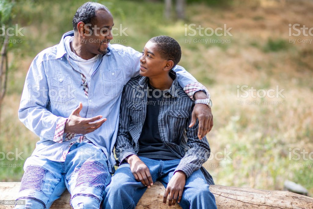An African American Father and Son have a talk in nature sitting on a...