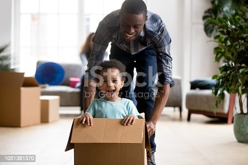 istock Black father and son playing with box at home 1051381370