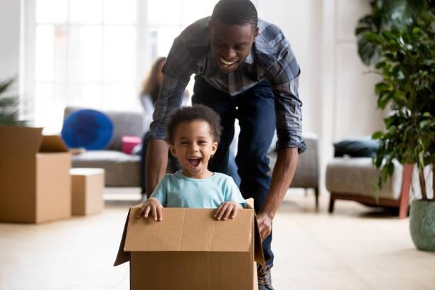 svart far och son leker med låda hemma - flyttlådor bildbanksfoton och bilder