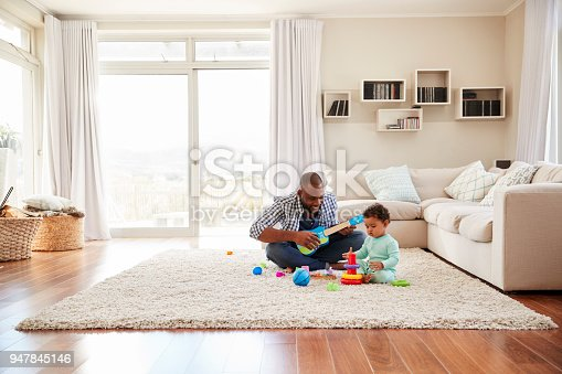 istock Black father and toddler son playing in the sitting room 947845146