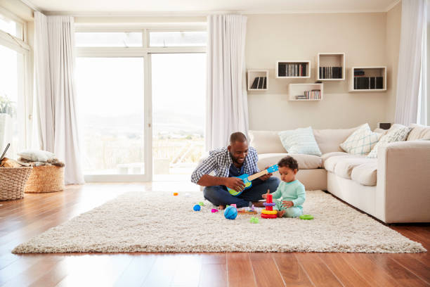 black father and toddler son playing in the sitting room - family room stock photos and pictures