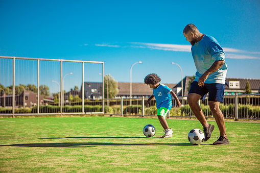 An african american father and young son playing soccer on a neighbourhood football pitch on a beautiful sunny day in the Netherlands