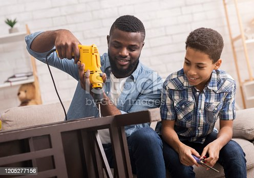 Black father teaching his son how to use drill, perforating chair in living room at home, sharing experience