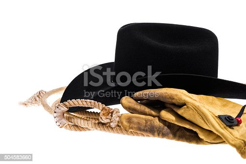 Close up of a side view of a black felt Cowbot hat, showing the black leather band, the crease and the pinch on the top of the crown of the hat sitting on a lasso with a pair of old, worn, dirty leather gloves isolated on white background