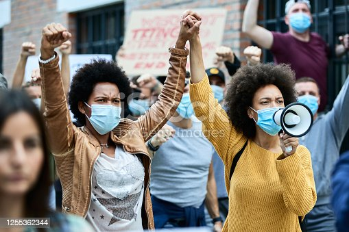 African American woman wearing protective face masks and holding hands while participating in demonstrations for human rights on the streets.