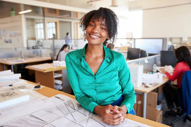 black female architect leans on desk smiling in busy office - persona in secondo piano foto e immagini stock