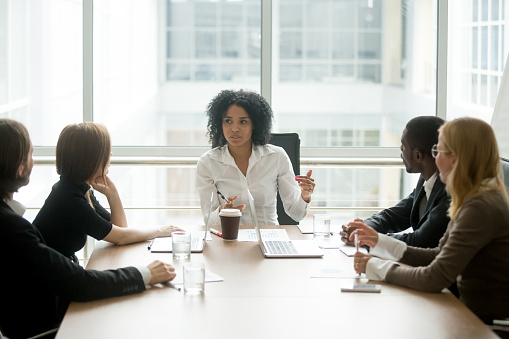 istock Black female boss leading corporate meeting talking to diverse businesspeople 923039680