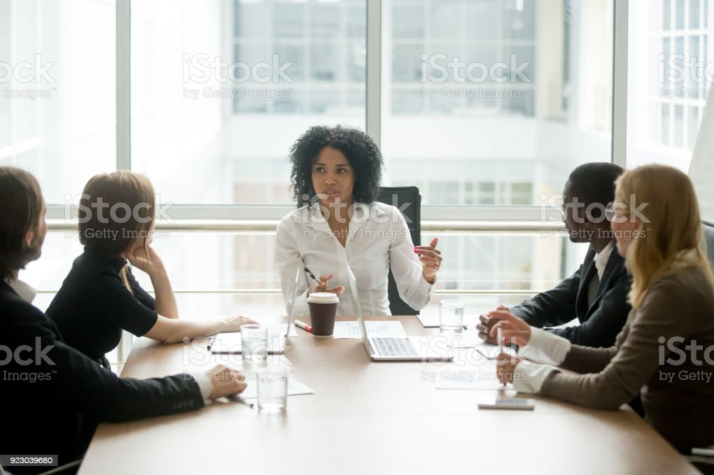 Black female boss leading corporate meeting talking to diverse businesspeople stock photo