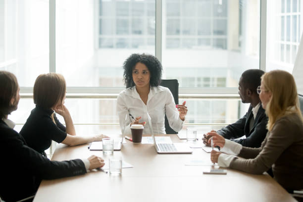 black female boss leading corporate meeting talking to diverse businesspeople - business meeting stock pictures, royalty-free photos & images