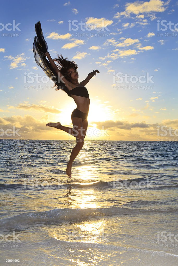 black female dancer leaping in air over the ocean stock photo