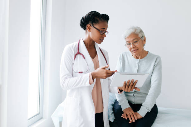 Black female doctor showing digital tablet to senior patient A black female doctor standing next to female patient and showing her something on digital tablet. face to face stock pictures, royalty-free photos & images