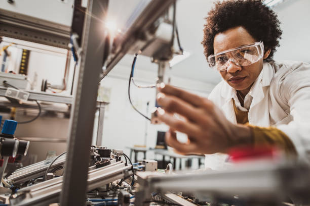 Black female engineer working on industrial machine in a laboratory. Low angle view of African American lab worker examining machine part while working in a lab. engineer stock pictures, royalty-free photos & images