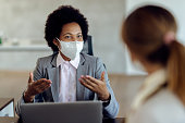 istock Black female financial consultant talking to her client and wearing protective face mask during the meeting. 1272458877