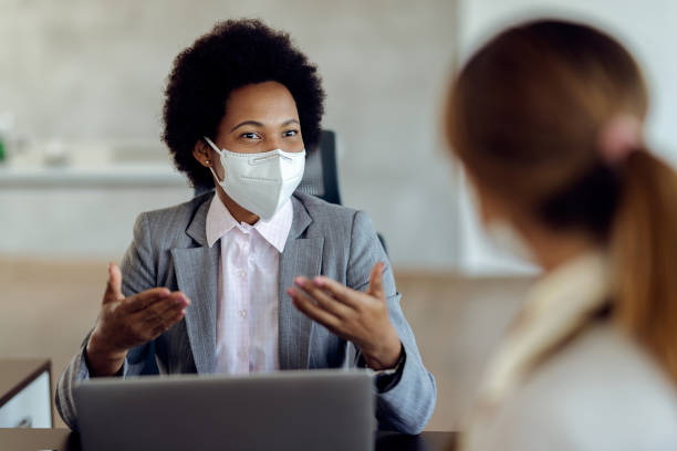 black female financial consultant talking to her client and wearing protective face mask during the meeting. - business stock pictures, royalty-free photos & images