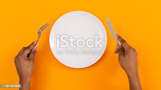 Lunch time. Top view of empty plate with fork and knife in black woman's hands on orange background, panorama