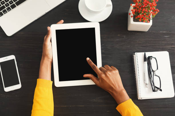 Black female hands on digital tablet, top view stock photo