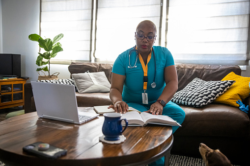 A black female nurse studying for another degree studies between her shifts