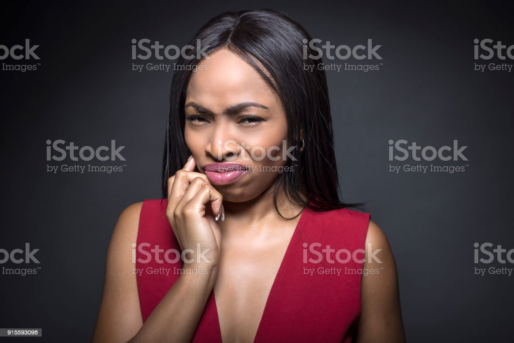 Black female on a dark background looking disgusted stock photo