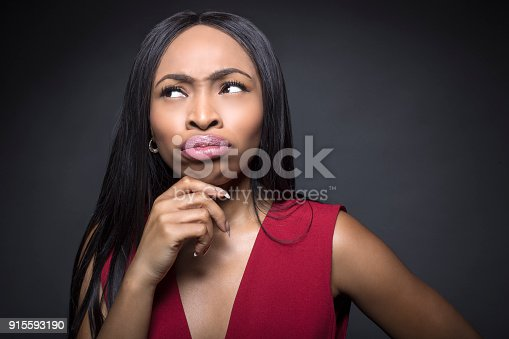 istock Black female on a dark background thinking or confused 915593190