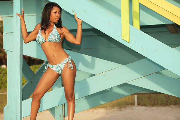Black female posing by a lifeguard hut Image of an attractive young black female posing in a bikini by a lifeguard hut on the beach middle aged women in bikinis stock pictures, royalty-free photos & images