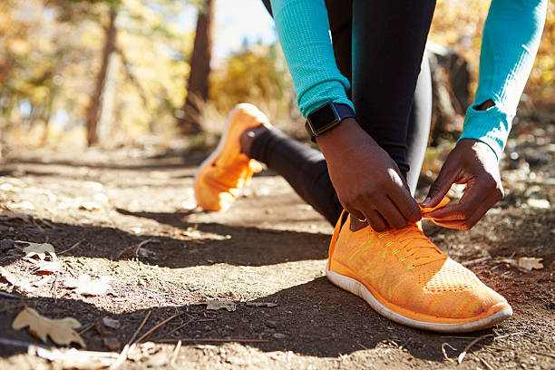 Black female runner in forest tying shoe, low section detail stock photo