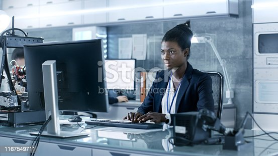 istock Black Female Scientist Working on a Computer with Her Colleagues at Research Center. 1167549711