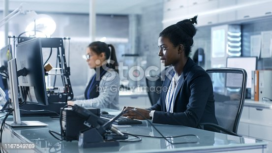 istock Black Female Scientist Working on a Computer with Her Colleagues at Research Center. Her Coworkers are Man and Female Caucasian. Laboratory is Modern. 1167549769