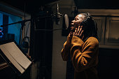 istock Black female singer singing into microphone in recording studio 1284317705