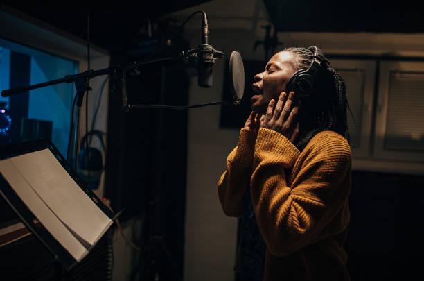 Black female singer singing into microphone in recording studio stock photo
