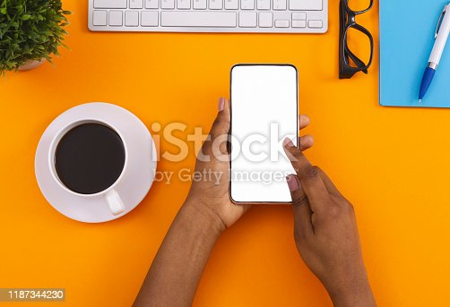 950613878 istock photo Black female using smartphone and drinking coffee at workplace 1187344230