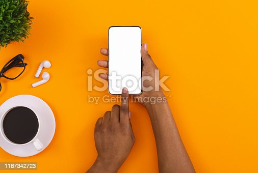 Top view of woman's hands using touching blank screen on smartphone, downloading app for listening music online in erphones, copy space