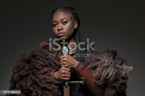 Sword wielding black viking zulu warrior female in studio shot