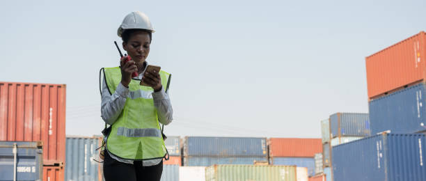 black foreman woman worker working checking at container cargo harbor holding radio walkie-talkie and smartphone to loading containers. african dock female staff business logistics import export shipping concept. - ricetrasmettitore foto e immagini stock