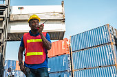 istock Black foreman worker working control the crane and forklift at Container cargo harbor to loading containers. African dock male staff with radio walkie-talkie for Logistics import export shipping concept. 1219005554