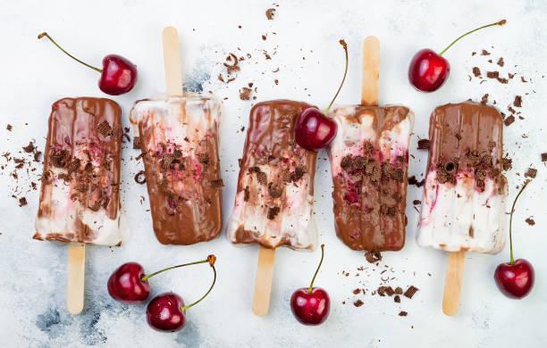 schwarzwald schokoladenfondant eis am stiel mit gebratenen kirschen und kokoscreme. vegan - schokolade gebratene kuchen stock-fotos und bilder