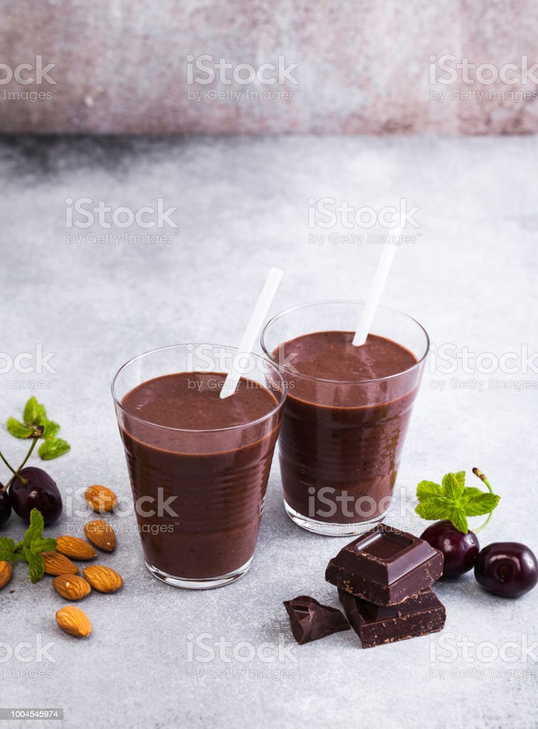 Black forest smoothies on the gray surface of the table. chocolate milk shake with nuts and cherries stock photo