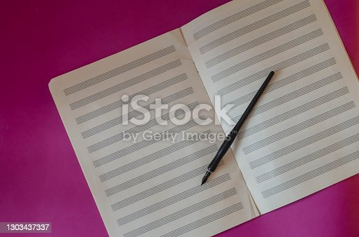 Black fountain pen and open music notebook on purple background. Musical creativity. Flat lay. Copy space.