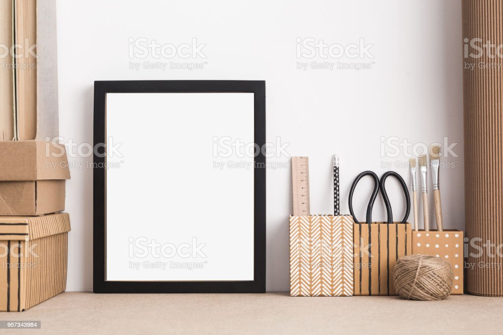 Black frame mock up in styled modern artist workspace with brushes; scissors; dummy. stock photo